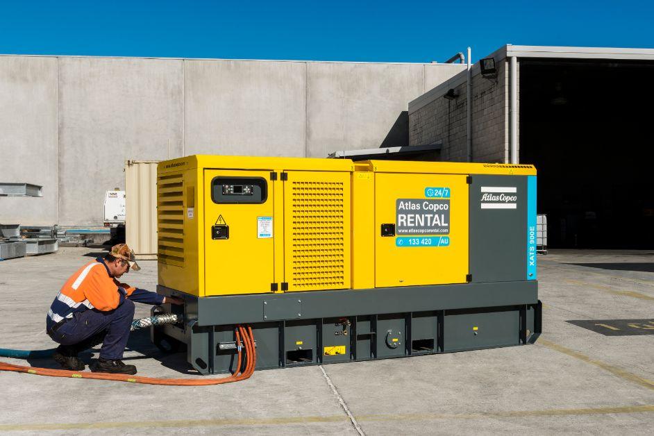 Comp4mfg technician installing an Atlas Copco air compressor rental on-site. Rental Air Compressor. Compressors For Manufacturing.